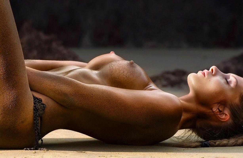 Голые сисечки у девахи лежащей на песке