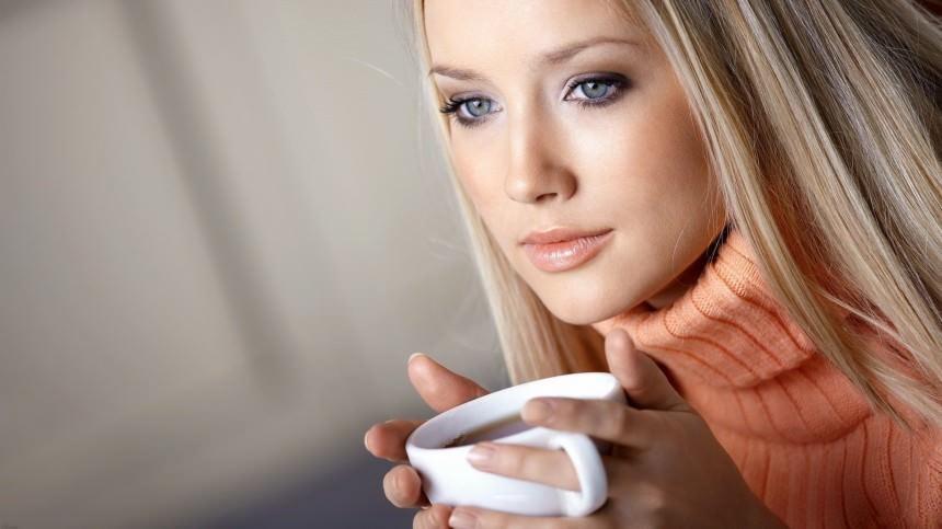 Милая девушка пьет горячий кофе в